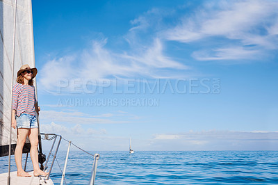 Buy stock photo Full length shot of an attractive mature woman enjoying a boat cruise out on the ocean