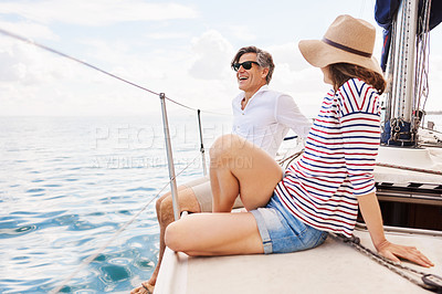 Buy stock photo Full length shot of an affectionate mature couple enjoying a boat cruise out on the ocean