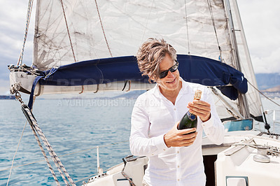 Buy stock photo Cropped shot of a handsome mature man opening a bottle of champagne while enjoying a boat cruise out on the ocean