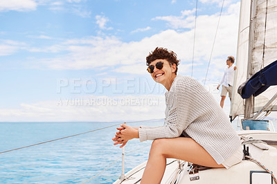 Buy stock photo Cropped shot of an attractive mature woman enjoying a boat cruise out on the ocean with her husband in the background