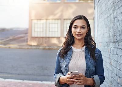 Buy stock photo Portrait of an attractive young woman using her cellphone while out in the city