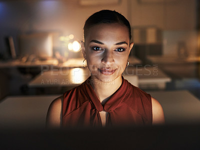 Buy stock photo Shot of a beautiful young woman using a computer while working late in her office during the evening