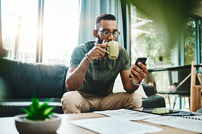 Buy stock photo Shot of a young man using a smartphone while going over his finances at home