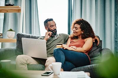 Buy stock photo Shot of a young couple using a credit card while going over their finances at home