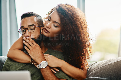 Buy stock photo Shot of a young woman hugging her husband who looks worried while using a laptop at home