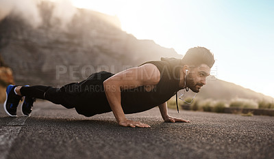 Buy stock photo Shot of a sporty young man doing pushups while exercising outdoors