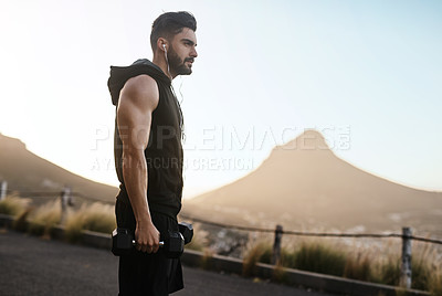 Buy stock photo Shot of a sporty young man exercising with weights outdoors