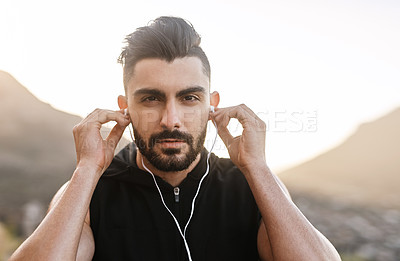 Buy stock photo Portrait of a young man listening to music while exercising outdoors