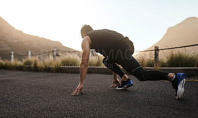 Buy stock photo Rearview shot of a sporty young man in starting position while exercising outdoors