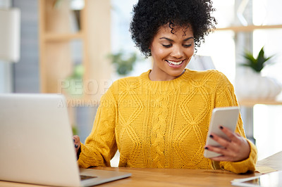 Buy stock photo Cropped shot of a beautiful young woman using her cellphone while sitting with her laptop