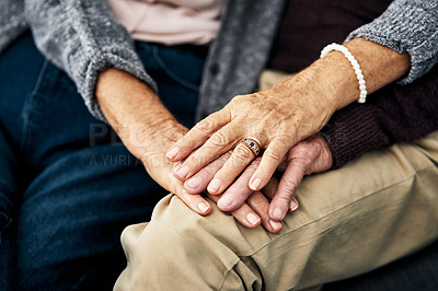 Buy stock photo Cropped shot of an unrecognizable senior couple's hands as they sit on their living room sofa at home
