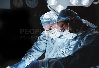 Buy stock photo Shot of two surgeons performing an operation in a hospital