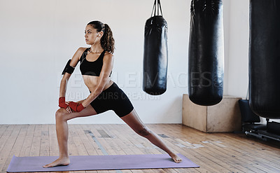 Buy stock photo Full length shot of a young sportswoman stretching during a workout session indoors