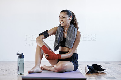 Buy stock photo Full length shot of an attractive young sportswoman siting down and resting after a workout session indoors