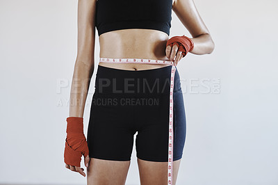 Buy stock photo Shot of an unrecognizable sportswoman measuring her waist against a grey background