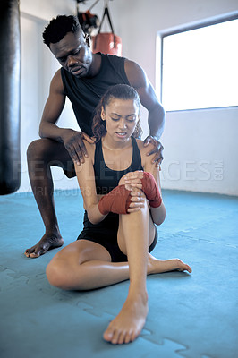 Buy stock photo Full length shot of a young fitness coach consoling an athlete after sustaining an injury at the gym