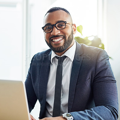 Buy stock photo Cropped shot of a young businessman using his laptop while sitting at his desk
