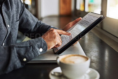 Buy stock photo Cropped shot of an unrecognizable man using a digital tablet while sitting in a coffeeshop