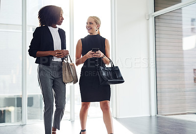 Buy stock photo Shot of two young businesswoman walking and having a conversation together inside a building