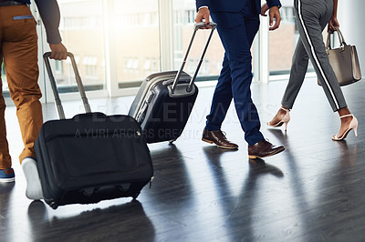 Buy stock photo Shot of unrecognizable businesspeople walking with their travel bags inside a building