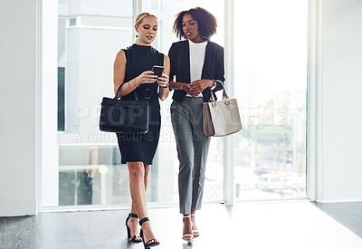 Buy stock photo Full length shot of two young businesswoman using a cellphone together while walking inside of a building