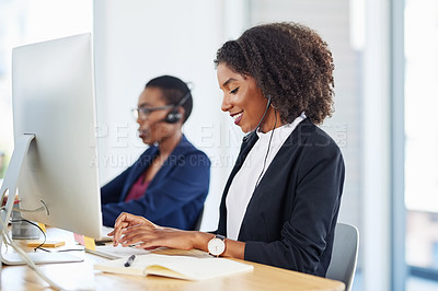 Buy stock photo Shot of a young call centre agent working alongside her colleague in an office