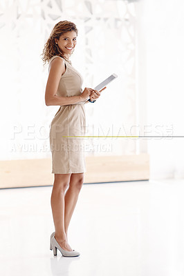 Buy stock photo Full length portrait of an attractive young businesswoman using her tablet while standing in the office