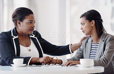 Buy stock photo Cropped shot of an attractive young businesswoman being consoled by a female colleague in their workplace