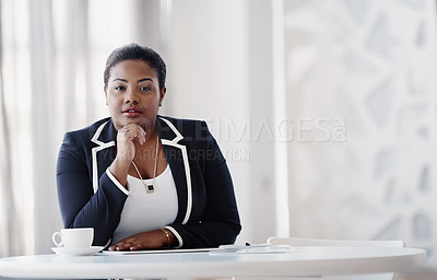 Buy stock photo Cropped portrait of an attractive young businesswoman sitting behind a desk in the office with her hand on her chin