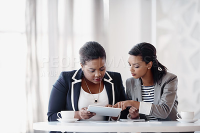 Buy stock photo Cropped shot of two attractive young businesswomen working together behind a desk in their office