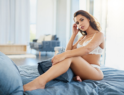 Buy stock photo Full length shot of a beautiful young woman in lingerie sitting on her bed in her bedroom at home