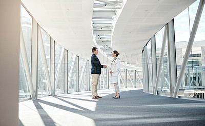 Buy stock photo Shot of a well dressed man shaking hands with a female doctor