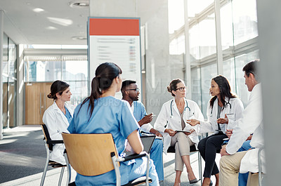 Buy stock photo Shot of a group of medical workers having a discussion while sitting together