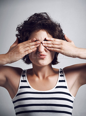 Buy stock photo Studio shot of an attractive young woman covering her eyes with her hands against a grey background