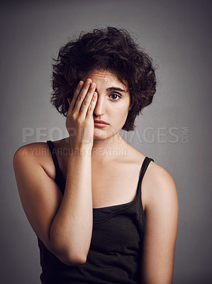 Buy stock photo Studio portrait of an attractive young woman covering her eye with her hand against a grey background
