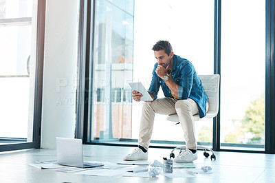Buy stock photo Shot of a young businessman brainstorming with a digital tablet and paperwork on a floor in an office