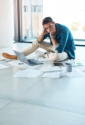 Buy stock photo Shot of a young businessman looking stressed out while working on a floor in an office