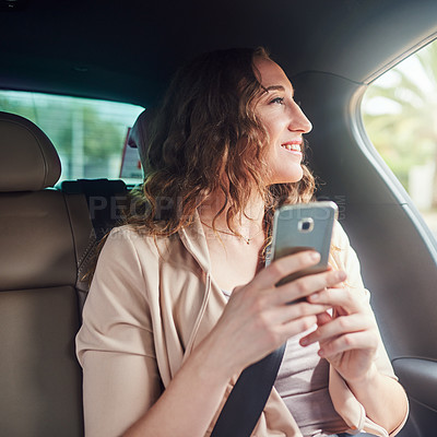 Buy stock photo Shot of an attractive young businesswoman using her cellphone while travelling in the backseat of a car