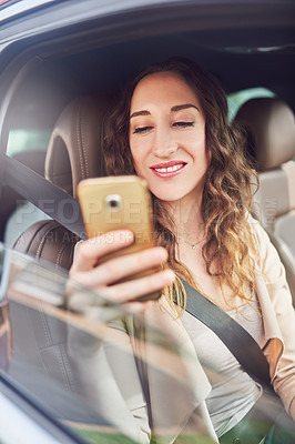 Buy stock photo Shot of an attractive young businesswoman using her cellphone while traveling in her car during the day