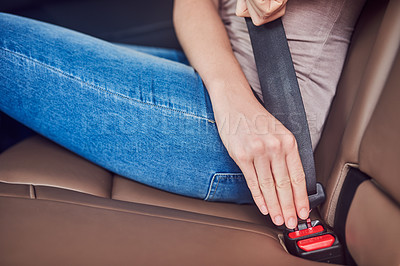 Buy stock photo Shot of an unrecognizable woman fastening her safety belt inside of a car