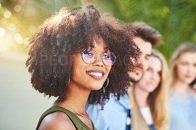 Buy stock photo Portrait of a group of cheerful young friends standing together arms around outside in the afternoon