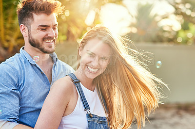 Buy stock photo Cropped shot of a cheerful young couple holding each other outside in the afternoon