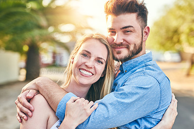 Buy stock photo Portrait of a cheerful young couple holding each other outside in the afternoon
