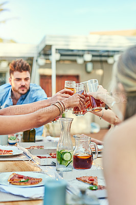 Buy stock photo Cropped shot of a group of young friends enjoying a meal and having a celebratory drink together outside in the afternoon