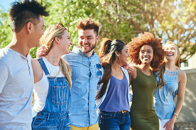 Buy stock photo Cropped shot of a group of cheerful young friends standing arms around outside in the afternoon