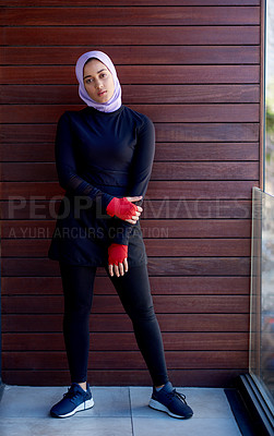 Buy stock photo Full length portrait of an attractive young woman wearing a headscarf and standing against a wooden background after her workout
