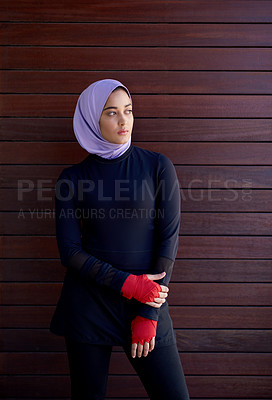 Buy stock photo Cropped shot of an attractive young woman wearing a headscarf and standing against a wooden background after her workout