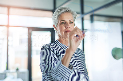 Buy stock photo Shot of a mature businesswoman writing down notes on a glass wall in her office