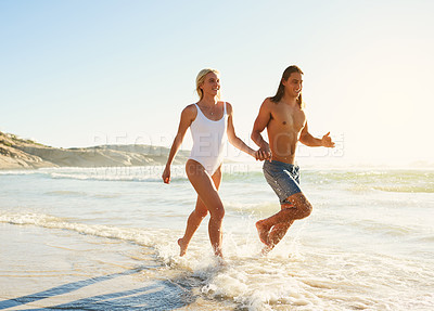 Buy stock photo Shot of a young couple running along the beach