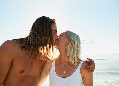 Buy stock photo Shot of an affectionate young couple kissing each other at the beach